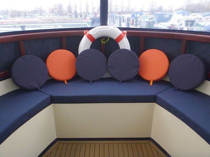 A re-upholstered boat seating area with porthole covers/cushions