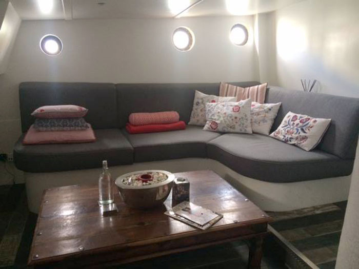 A re-upholstered yacht seating area with shaped foam cushions